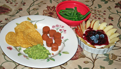 Guacamole and chips, sliced tofu dog, green beans and a yogurt desert with a border of sliced fuji apple with a mixed berry sauce drizzle topped with fresh blueberries.
